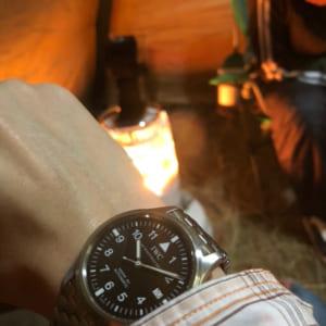 テントの中で腕時計をかざす姿